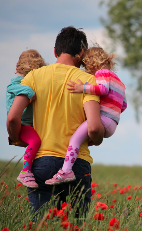 Adult carrying two children in a field