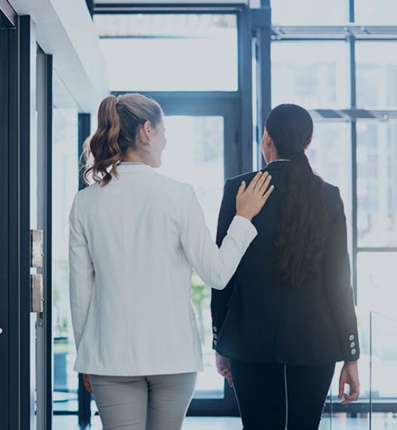 Two women walking through a door