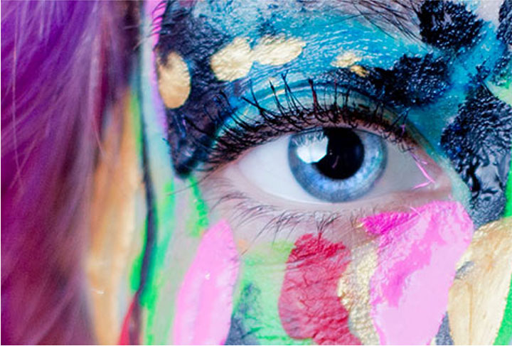 Close up on an eye. The surrounding face is covering in colourful paint