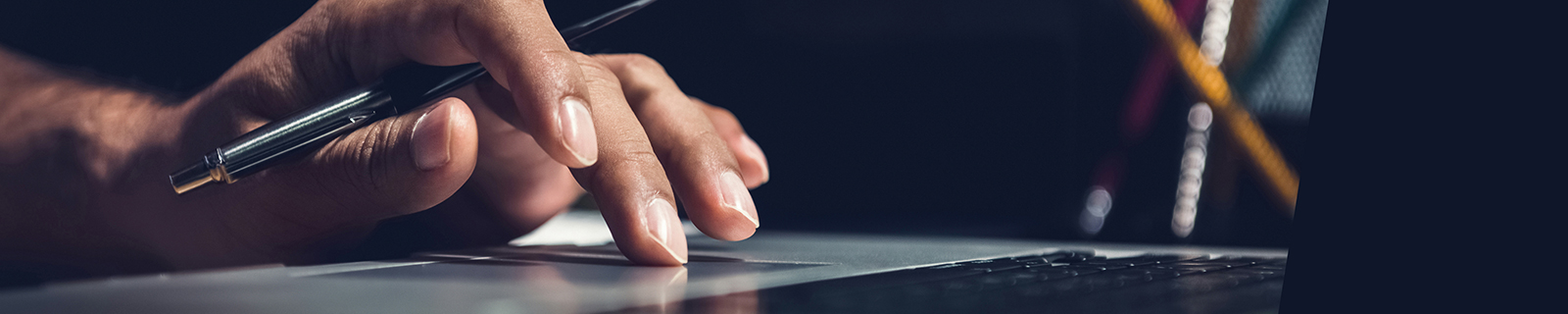 Person typing on a keyboard with a pen in hand