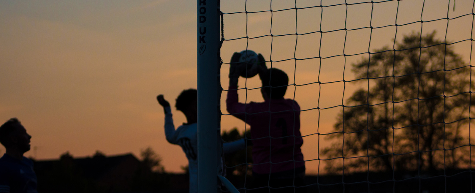 People playing football, the goalkeeper catching the ball