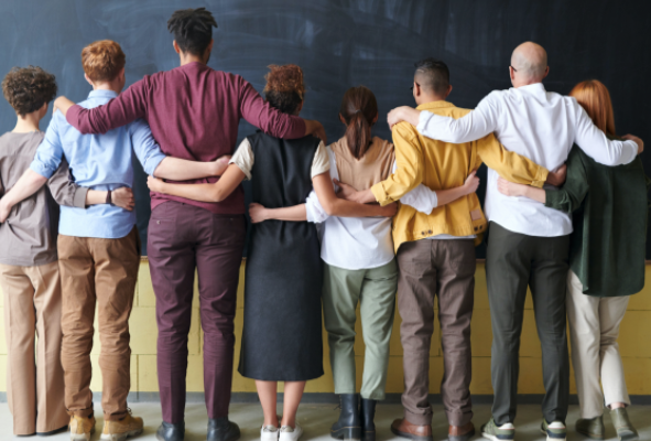 A group of people standing in front of a blackboard