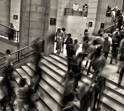 Black and white image of people walking up stairs