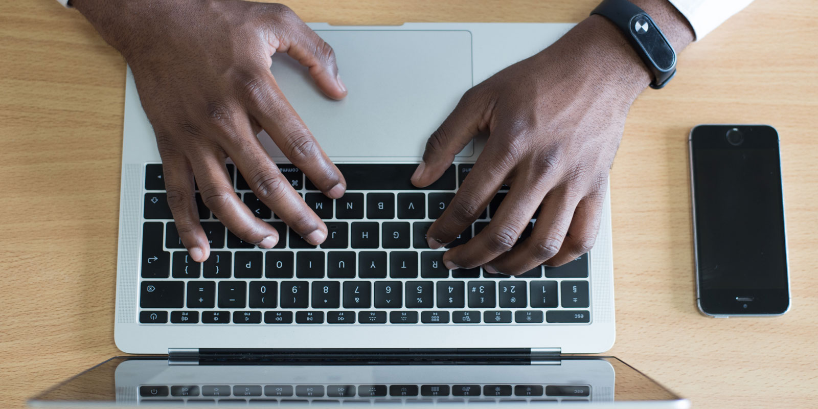 Top down view of a person typing on a laptop
