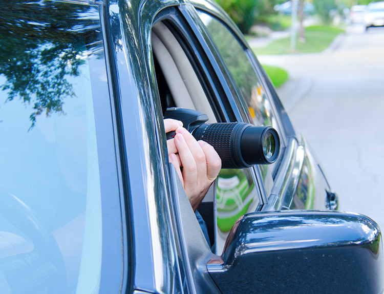 A camera being aimed out of a car window