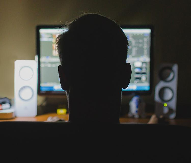A figure in silhouette sat at a computer